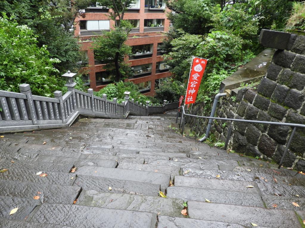 傾斜の緩い女坂。愛宕山の山麓を巻くように降りている。正面に赤レンガ色のビルがある。女坂の中ほどに赤い幟が立てられている。