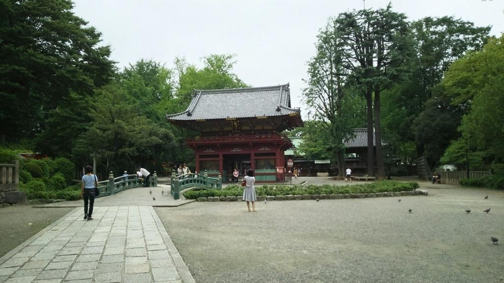 根津神社の境内全体の光景。中央に楼門があり、手前に神橋が架かっている。うっそうとした森に囲まれた空間を人々が散策している
