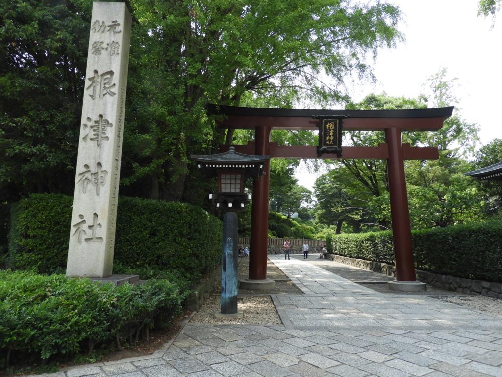 根津神社表参道のいりぐちにそびえる朱色の大鳥居。横に社号標が立っている。