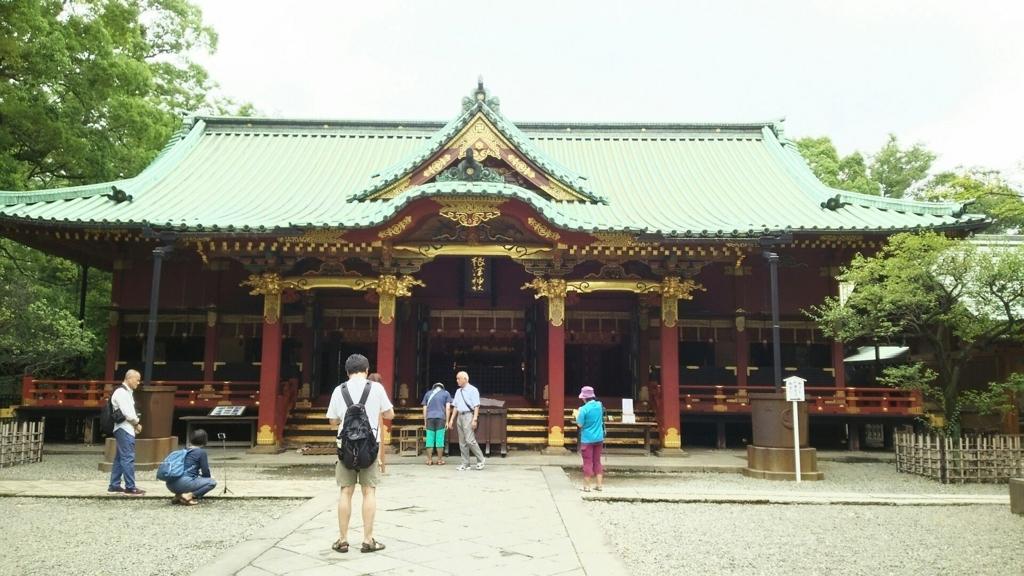 根津神社の拝殿。人々がお参りをしたり写真を撮ったりしている。