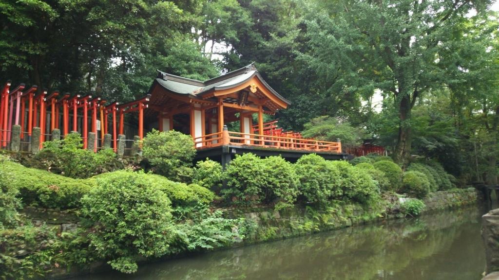 乙女稲荷神社の社殿。せりだした舞台の手前に池が広がっている。