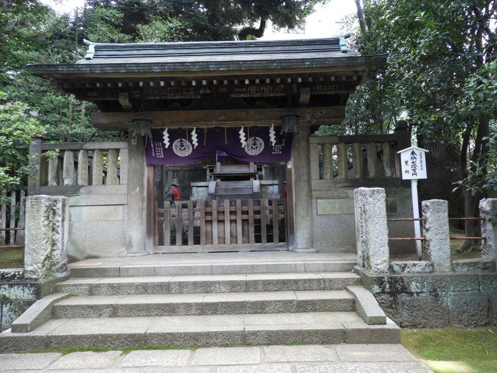 中央に駒込稲荷神社の門。手前に四段の石段がある。