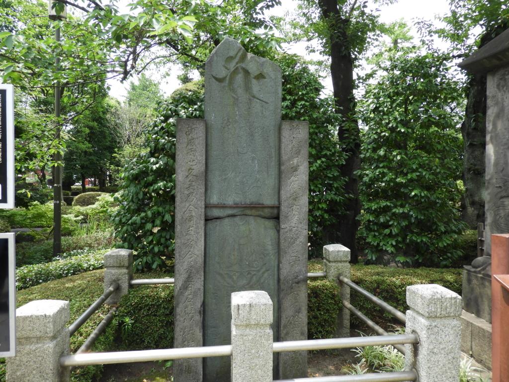 高さ3m近くあった西仏板碑。中央で折れているため、側柱を立てて支えている。