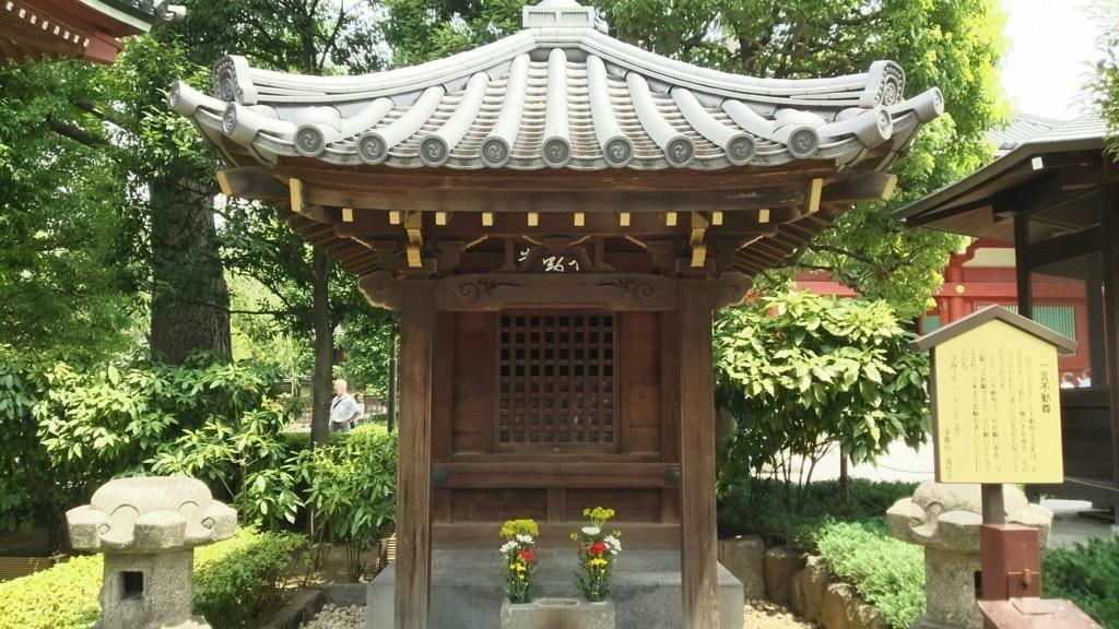 西境内の一言不動尊。左端に橋本薬師堂の庇が写っている。2本の生花が供えられている。