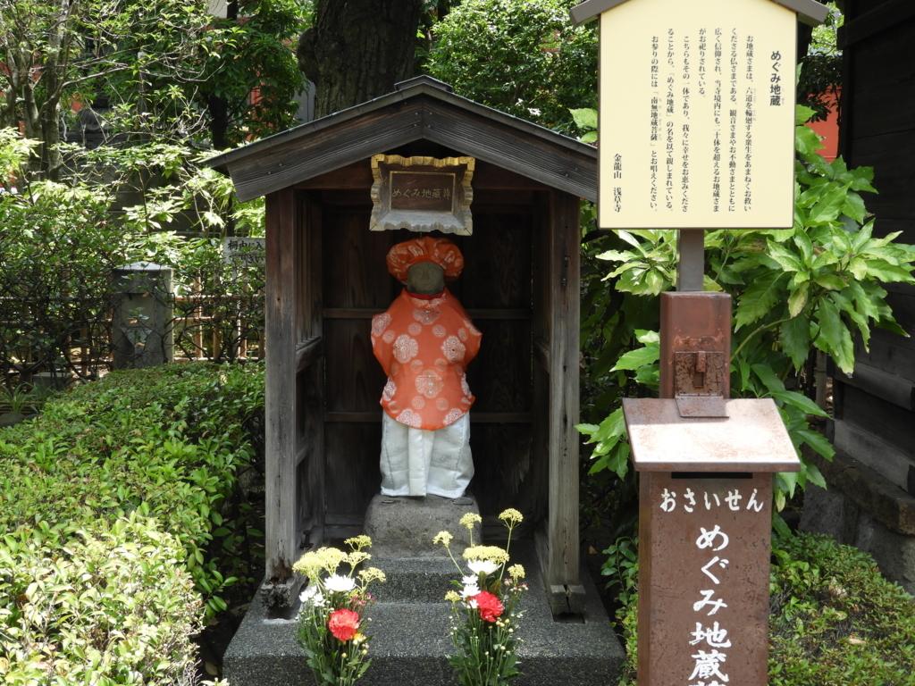 恵み地蔵。赤い衣装を着せられ、赤い帽子をかぶり、小さな祠の中に立っている。前には2本の生花が供えられている。