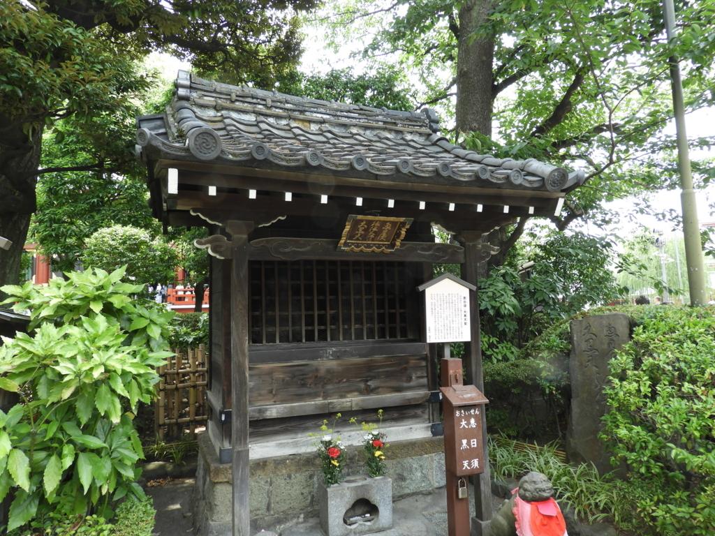 七福神の恵比寿と大黒天を祀るお堂。古い木造のお堂が周囲の緑に映えている。前に2本の生花が供えられている。