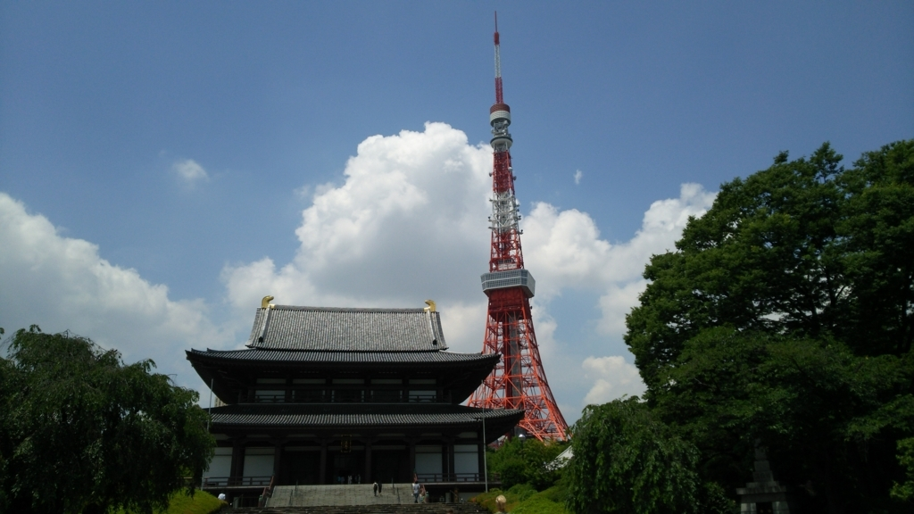 青空の下にある増上寺大殿。両側には濃い緑の樹木が植わっている。大殿のすぐ後ろに赤い東京タワーが立っている。