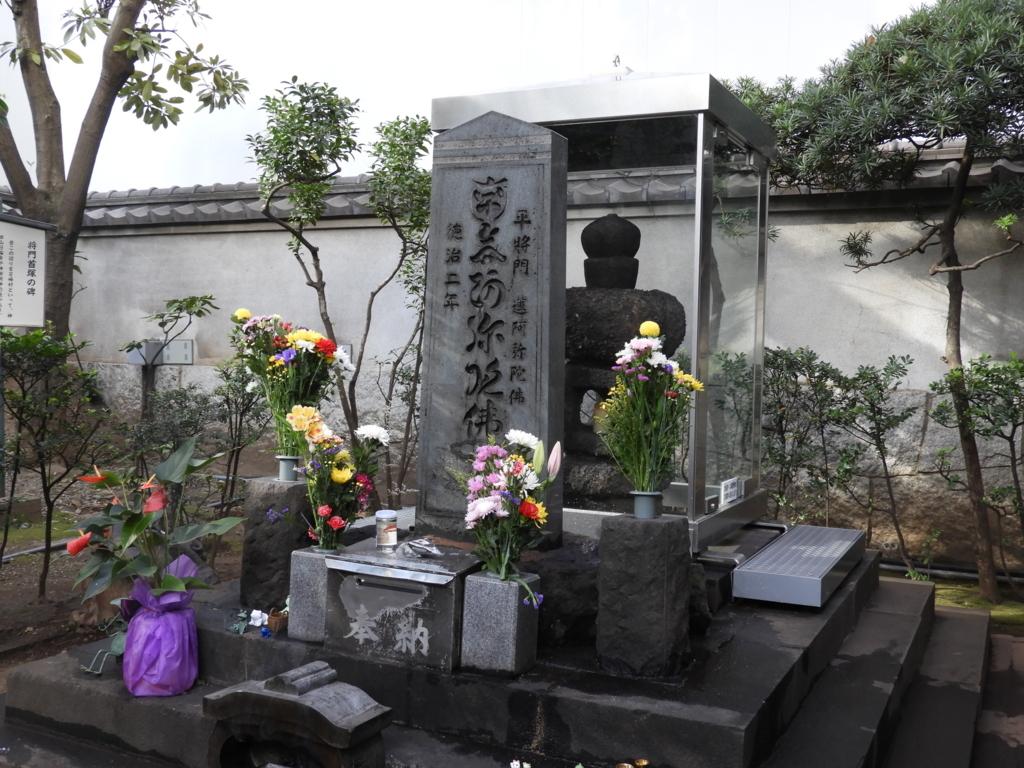 大手町の平将門の首塚。防護用のカバーで覆われ、清掃が行き届いた塚には多くの花が供えられている。