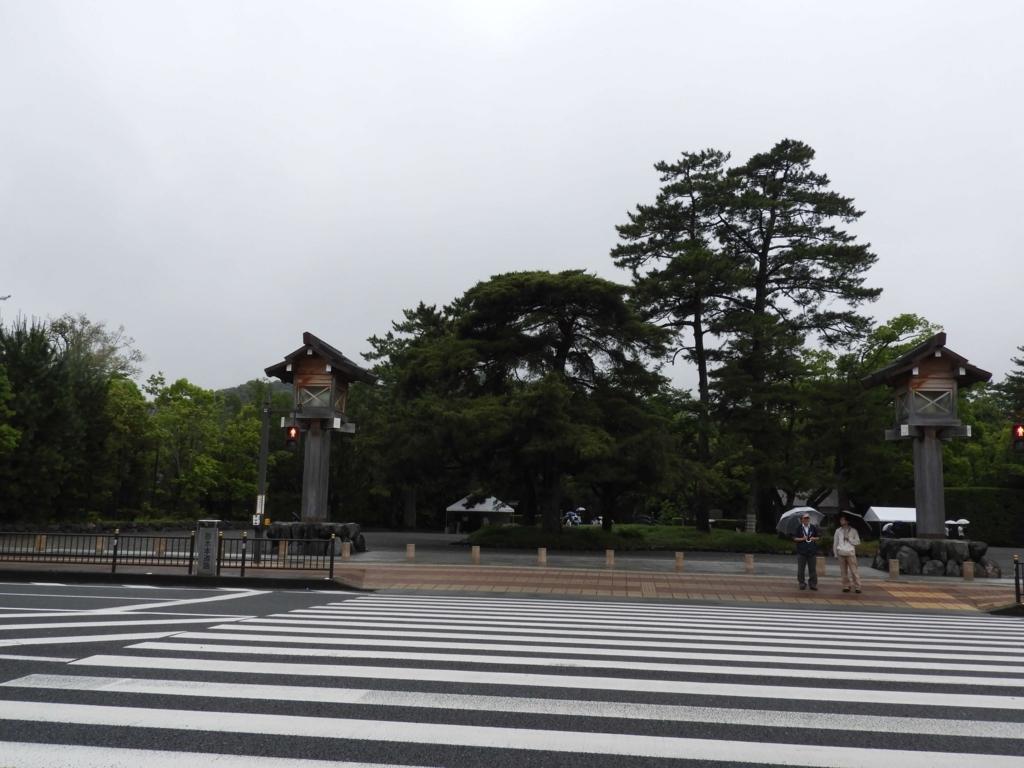 横断歩道の向こうに拡がる伊勢神宮の森。手前に傘をさした人が二人立っている。