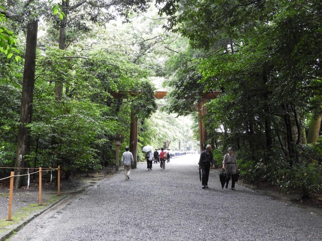 二の鳥居。うっそうとした森の中の参道の中央に立てられている。もう誰も傘をさしていない。