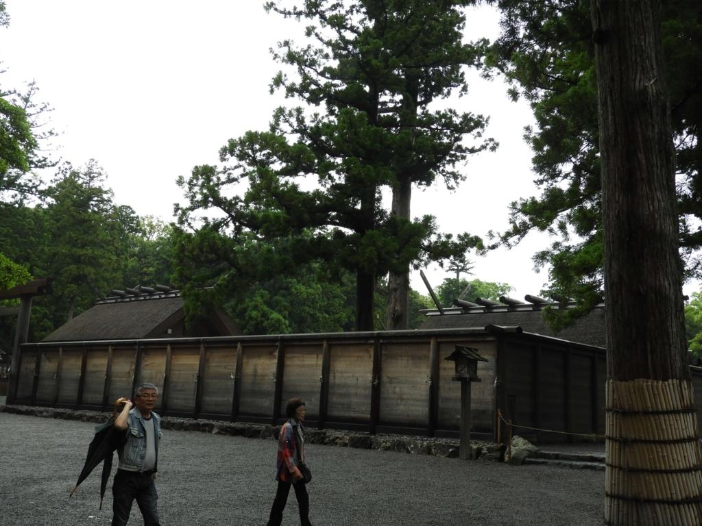 外宮正宮の壁とその上に見える社殿の屋根。手前を一組の老夫婦が歩いている。