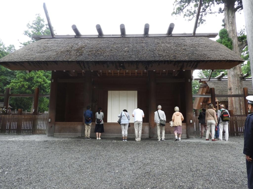 外宮正宮の拝殿。6人の人が拝み、4人の人が脇から奥を覗いている。入り口の脇にガードマンが立っている。