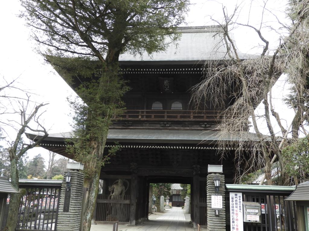 高安寺の山門。木造二階建ての堂々たる門であり、両脇に安置された仁王が目を光らせている。