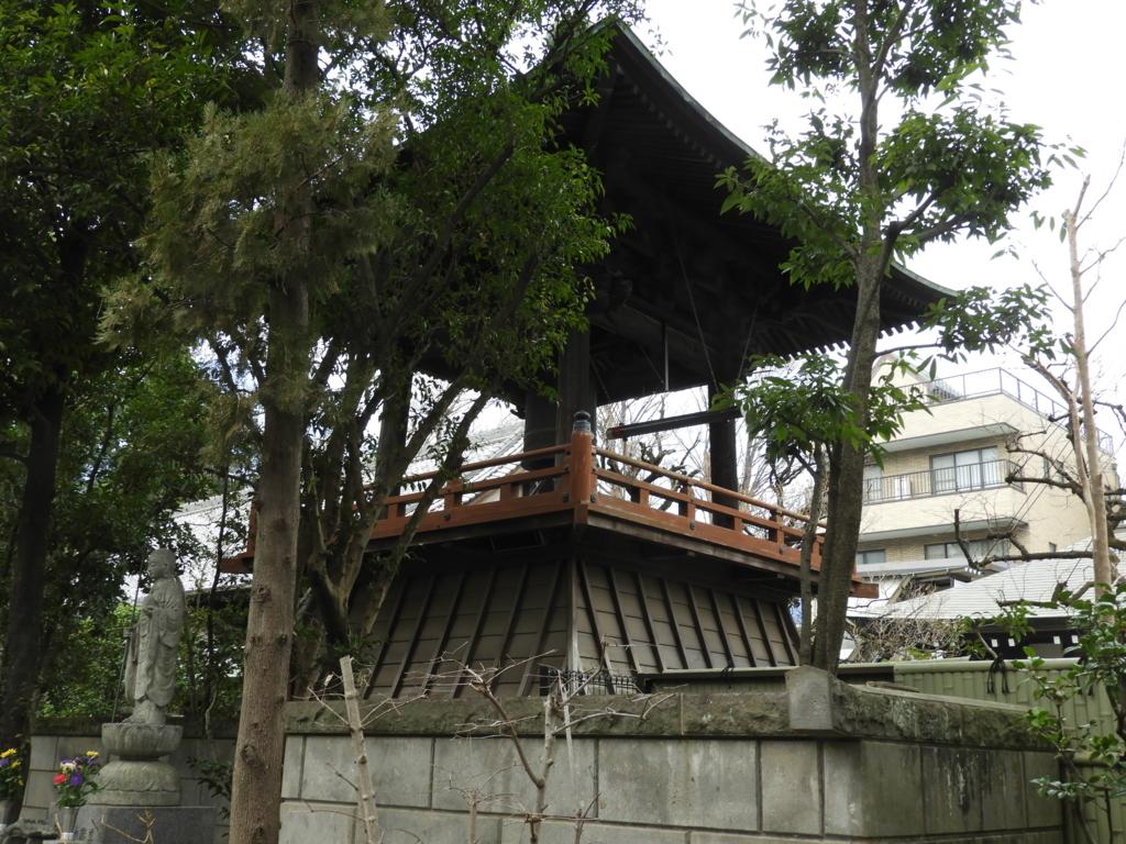 境内の木々の奥に設けられた鐘楼。時刻が来ると中央の橦木を自動で巻き上げて鐘を撞くn