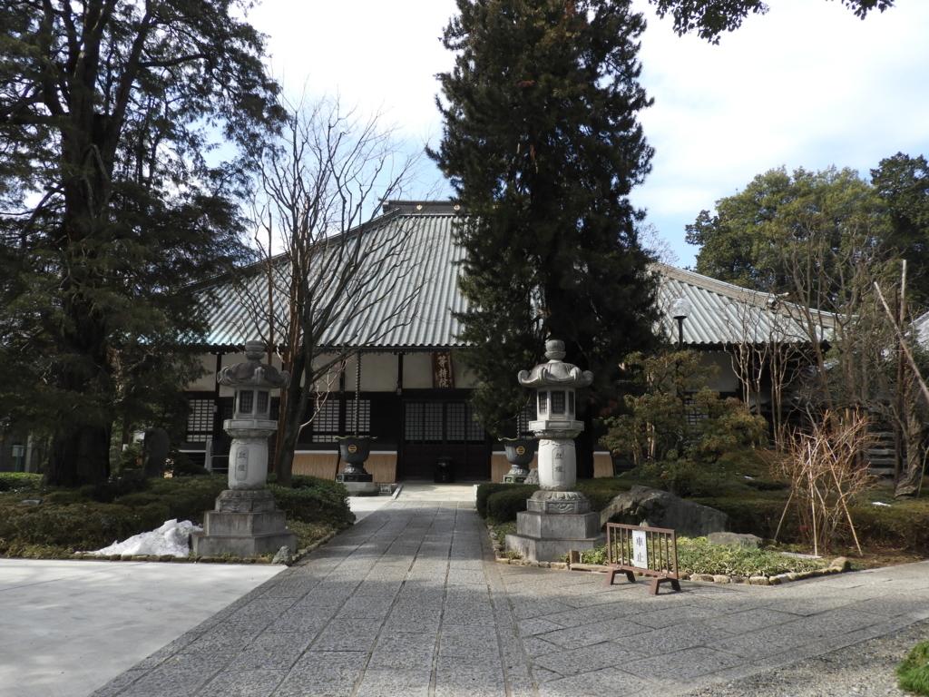 高安寺の本堂。手前に2本の巨木と2基の石灯籠がある。