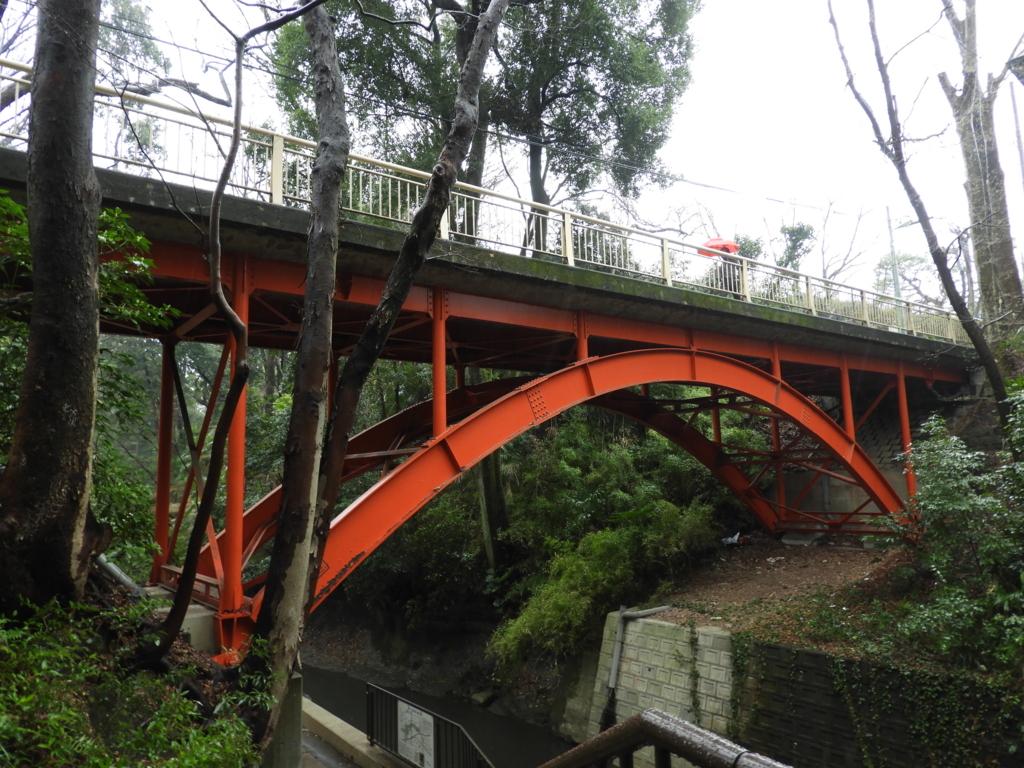 緑の渓谷をまたぐ朱色のゴルフ橋