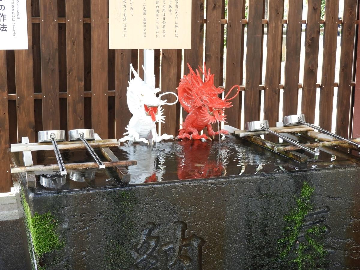 赤と白の二龍の口から水が出る手水舎