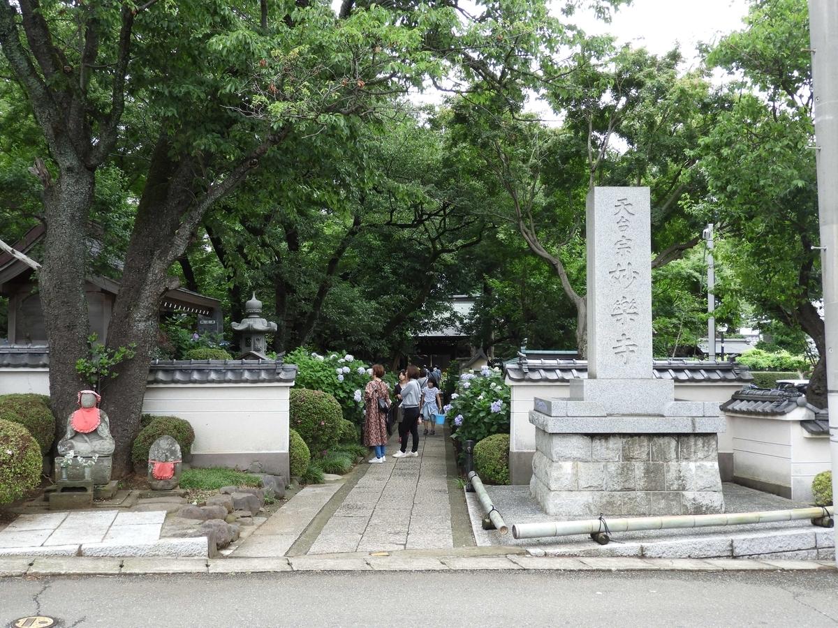 妙楽寺の寺号標とお参りしている人々