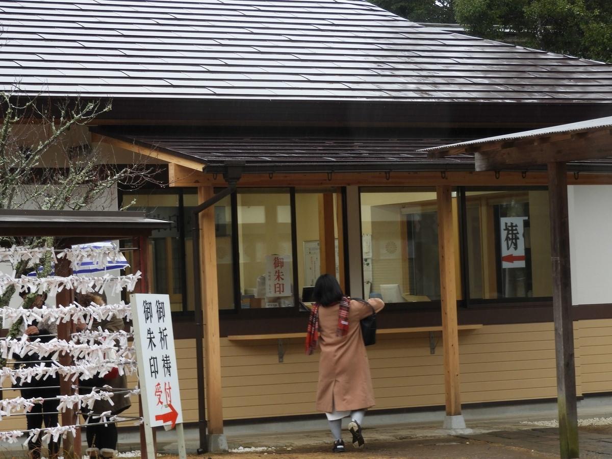 隋神門を入って右手の社務所。女性が一人向かっている。