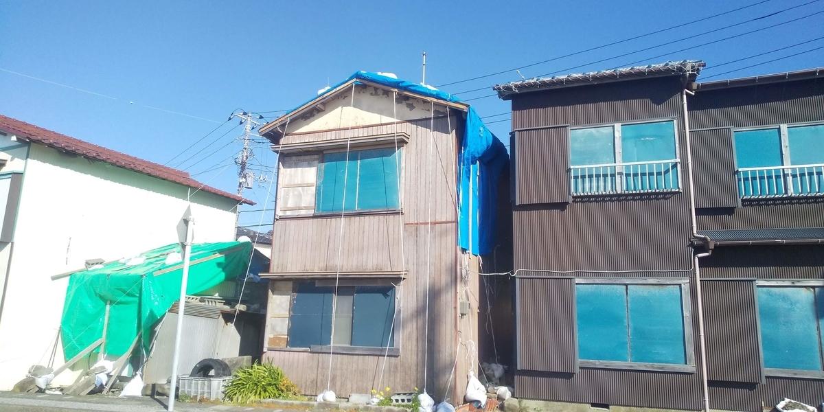 屋根をブルーシートで覆った家