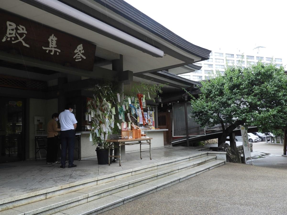 参集殿内の授与所。七夕の時期なので笹の葉が飾られている。2人の人が御朱印を待っている。