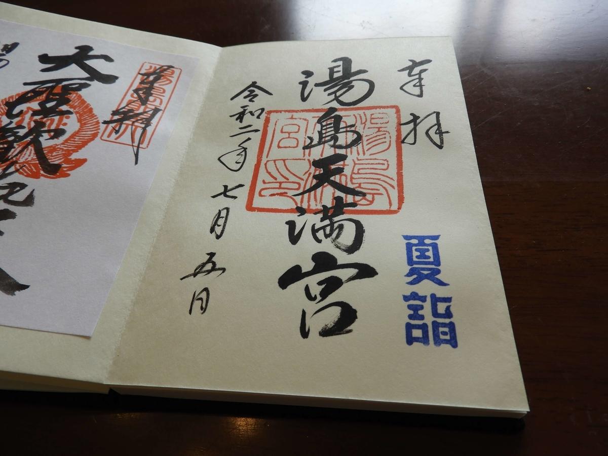 湯島天神の御朱印。「湯島天満宮」と温かみのある書体で書かれ、「夏詣 」と書かれた青い印が押されている。