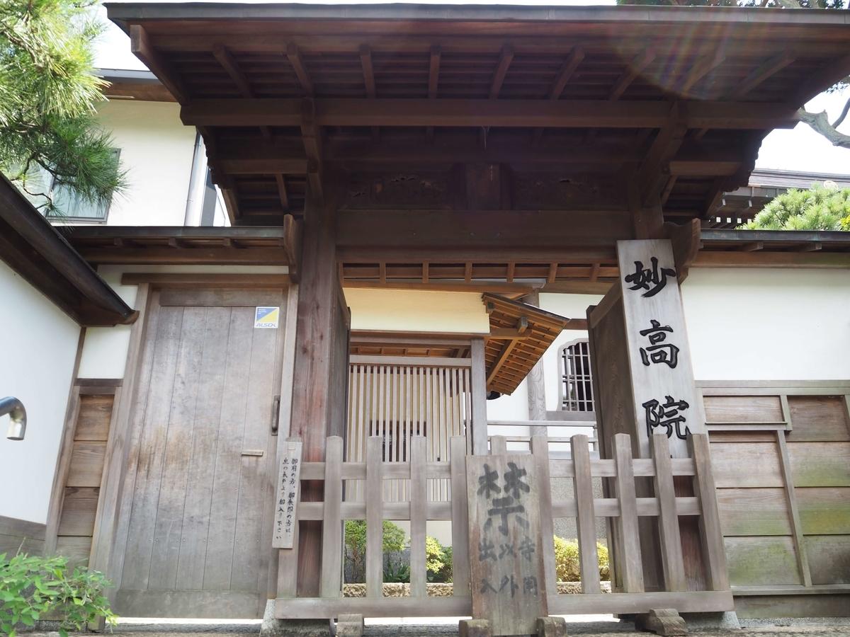 妙高院の門。閉まっているが左側の木戸に「御朱印の方はお入りください」と書かれた札がかかっている。