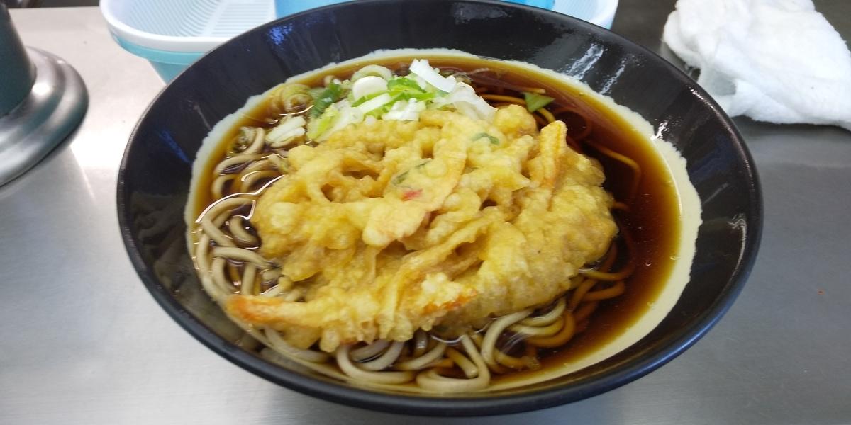 日栄軒の天ぷらそば。真っ黒なツユの上にしなしなの天ぷらがのっている