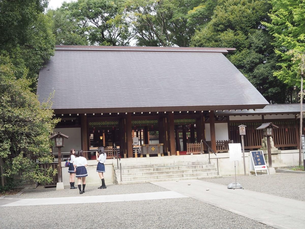 乃木神社の拝殿。女の子三人組が記念写真を撮っている