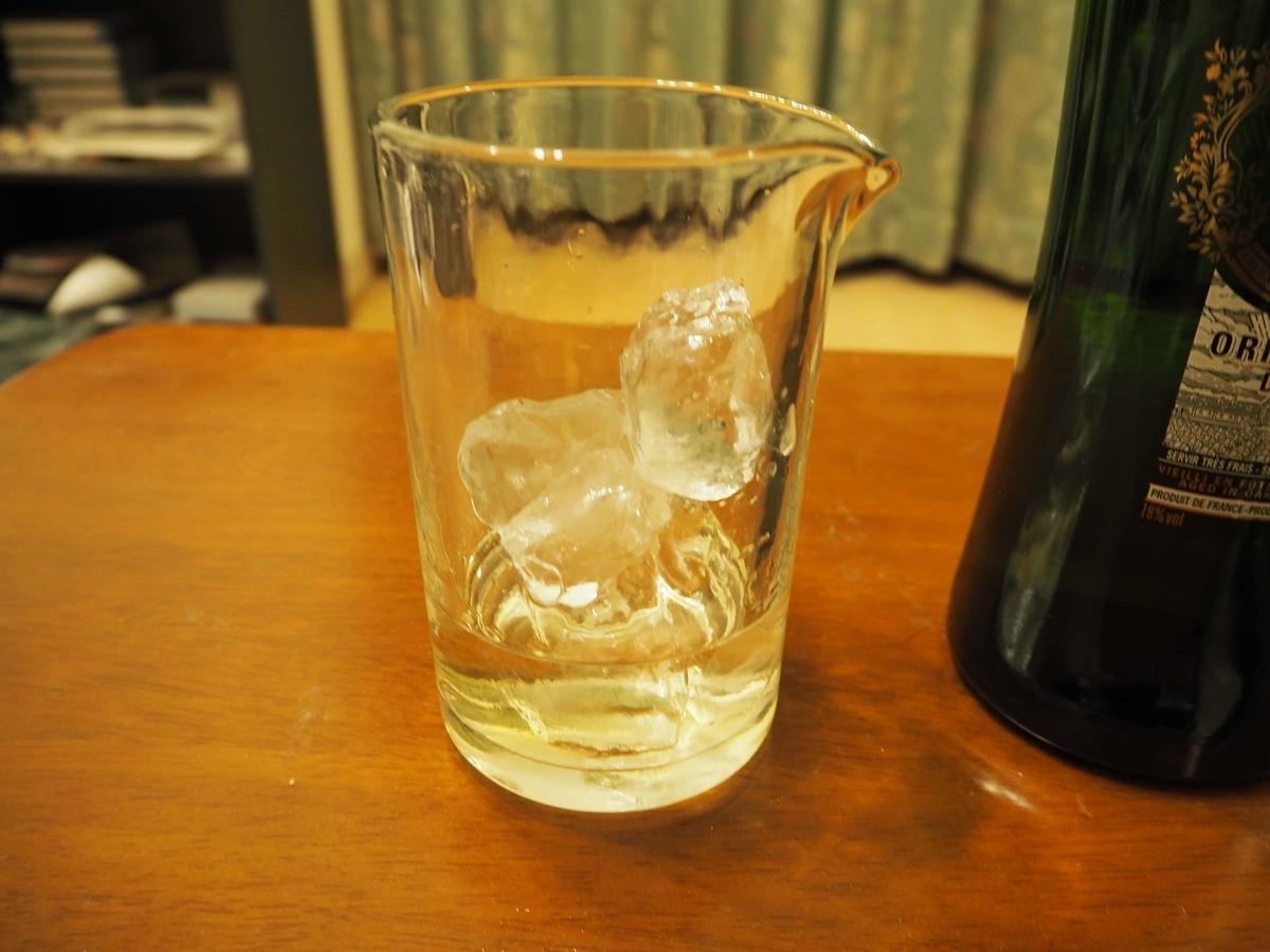 ミキシンググラスに入れた氷、ジン、ドライベルモット