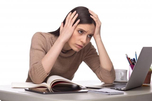 パソコンの前で頭を抱える人