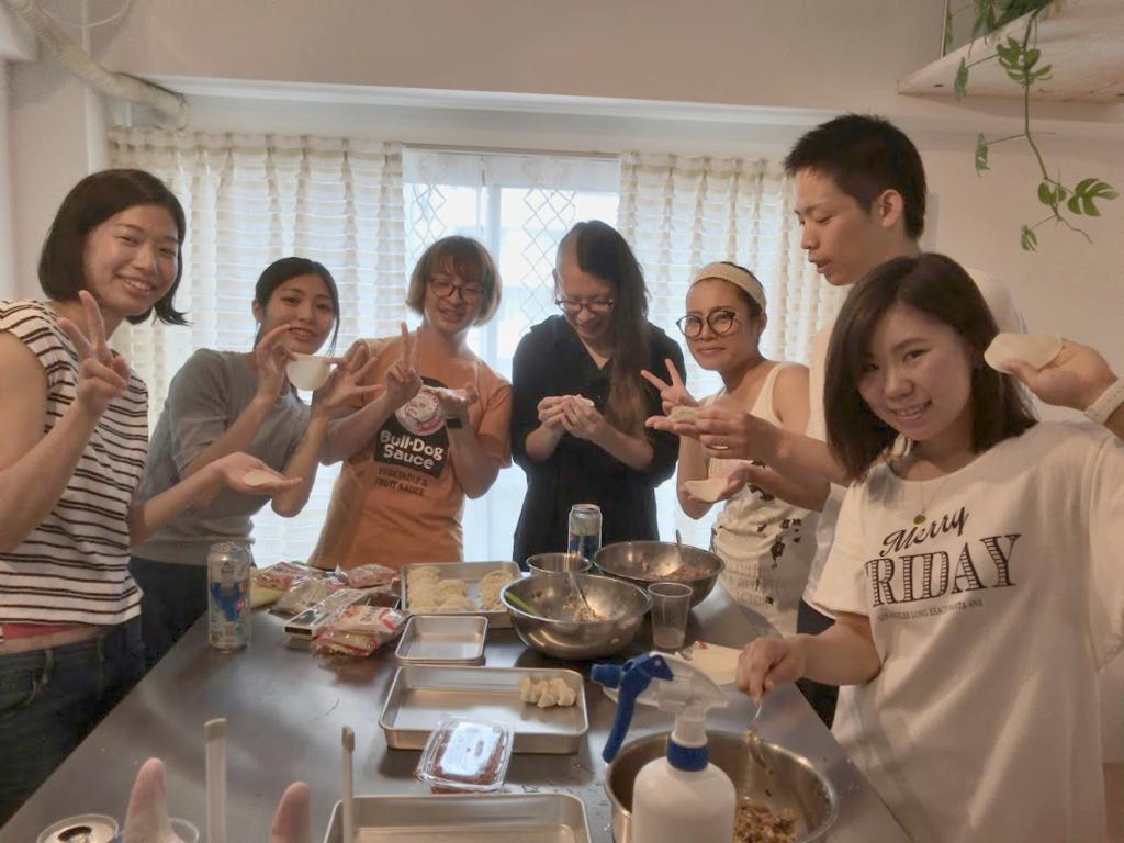 テーブルを囲んで餃子を作る面々の写真