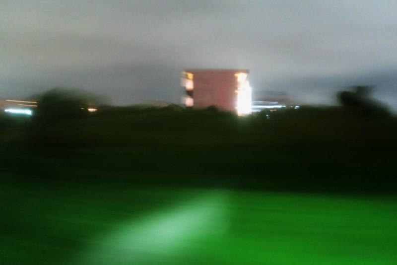 雨夜 車窓の団地とたんぼ
