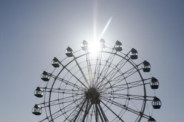 遊園地の観覧車に日の光が当たって反射している。