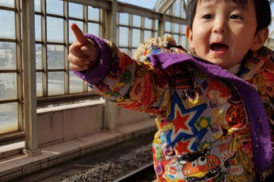 駅のホームで指をさす子ども