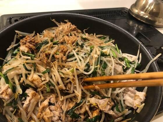 シマダヤの上海焼きそばの麺とソースとニラと豚肉ともやしを混ぜている