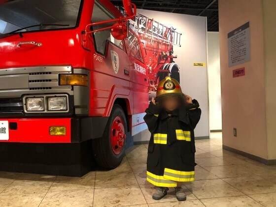 四谷にある消防博物館3階の消防車横で消防士さんの格好をして写真を撮っている子ども