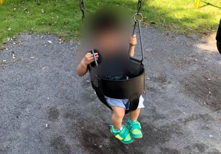 県立相模原公園のブランコに乗っている幼児
