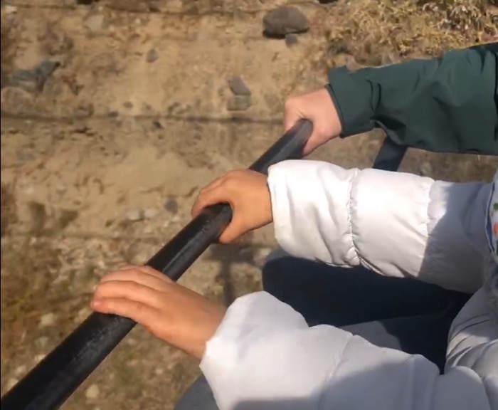清里テラスのリフトのハンドルをしっかりと握る子ども