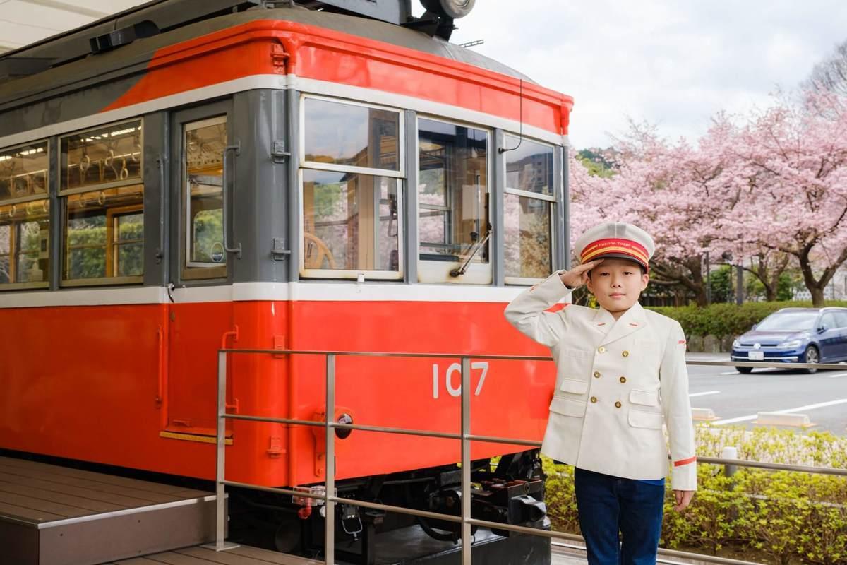 小田原鈴廣かまぼこの里にあるえれんなごっそcafe107の箱根登山鉄道の前で車掌さんの制服を着る子ども
