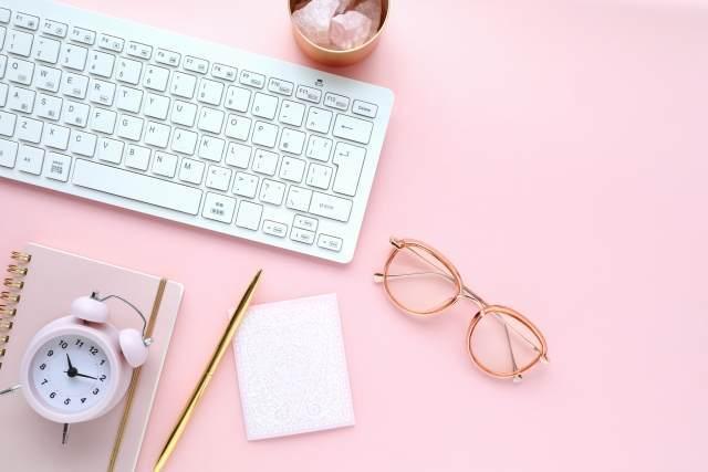ピンクの机にパソコンのキーボード
