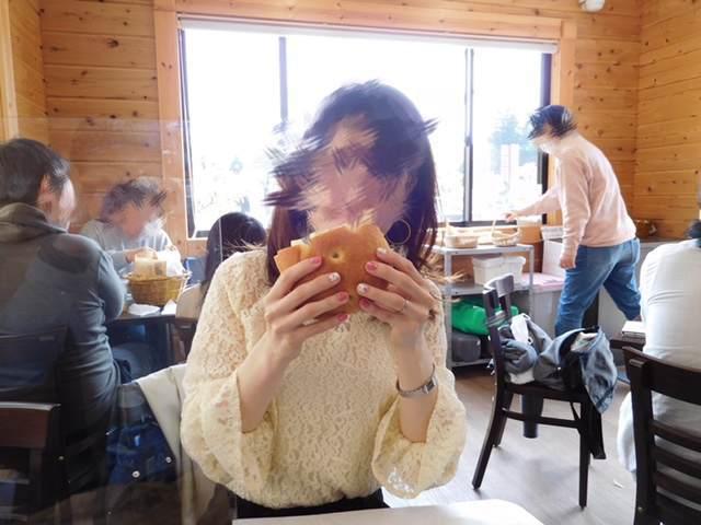 三島スカイウォークにあるピクニックカフェのバジルチキンサンドを食べる女性