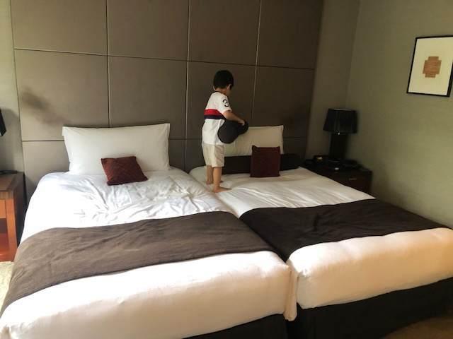 エクシブ箱根離宮のスタンダードグレードの部屋のベッドに乗っている子ども