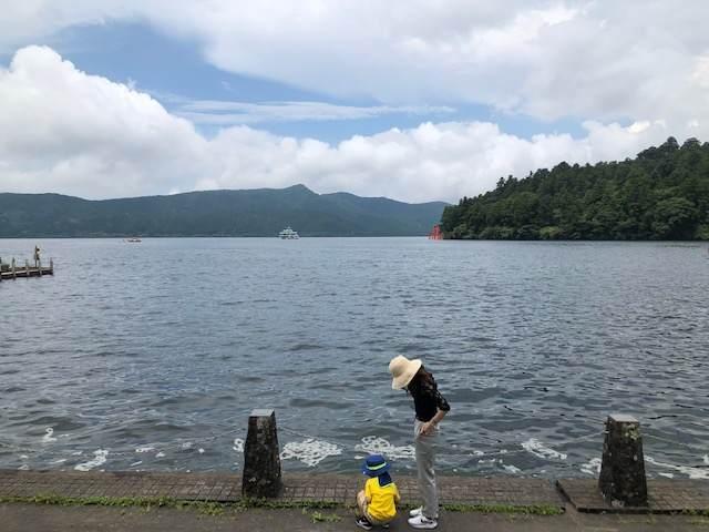 芦ノ湖のほとりに立つ子どもと女性