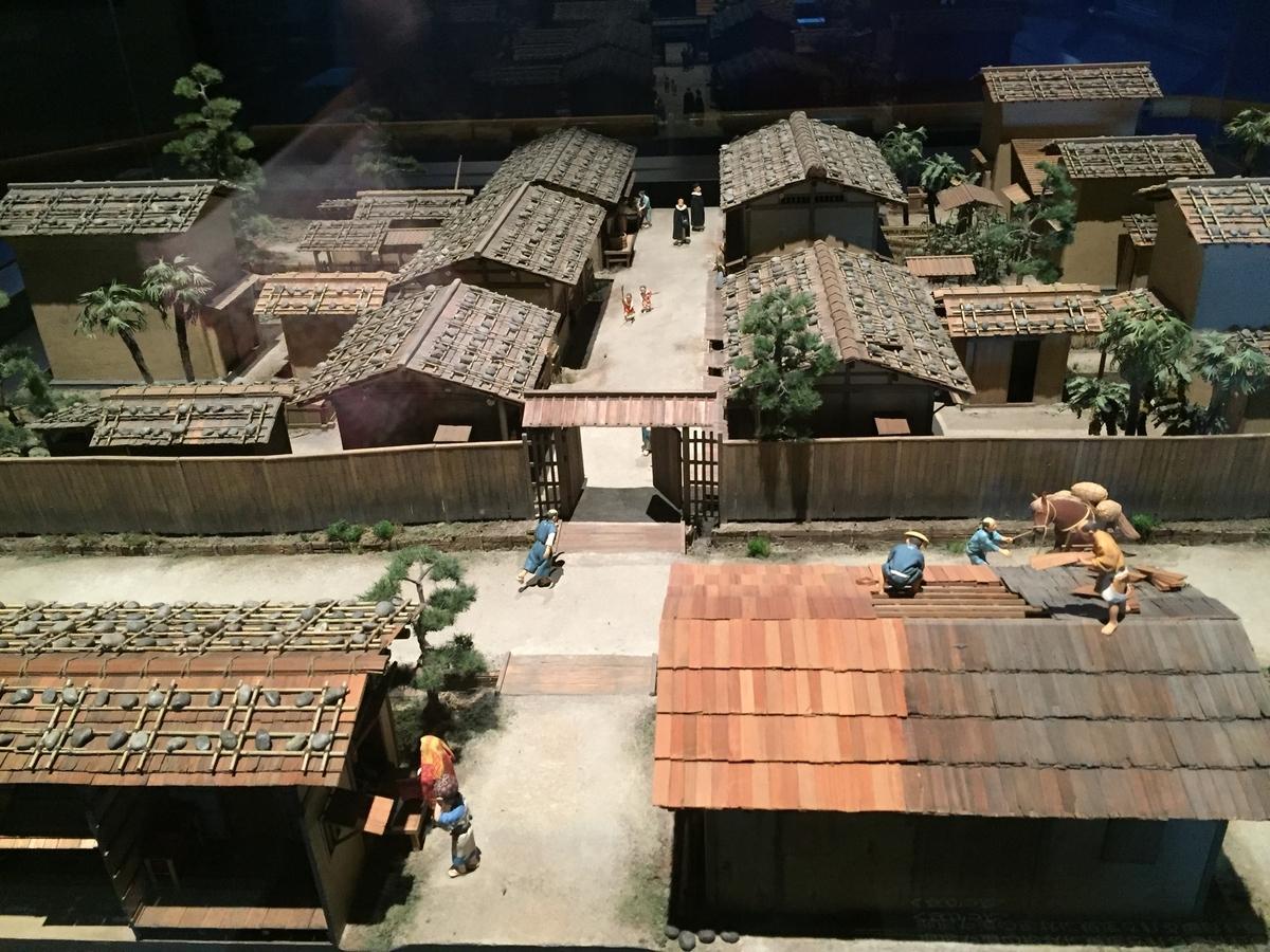 近世の大阪の町並みの模型、屋根を葺く人や子どもなども再現されている