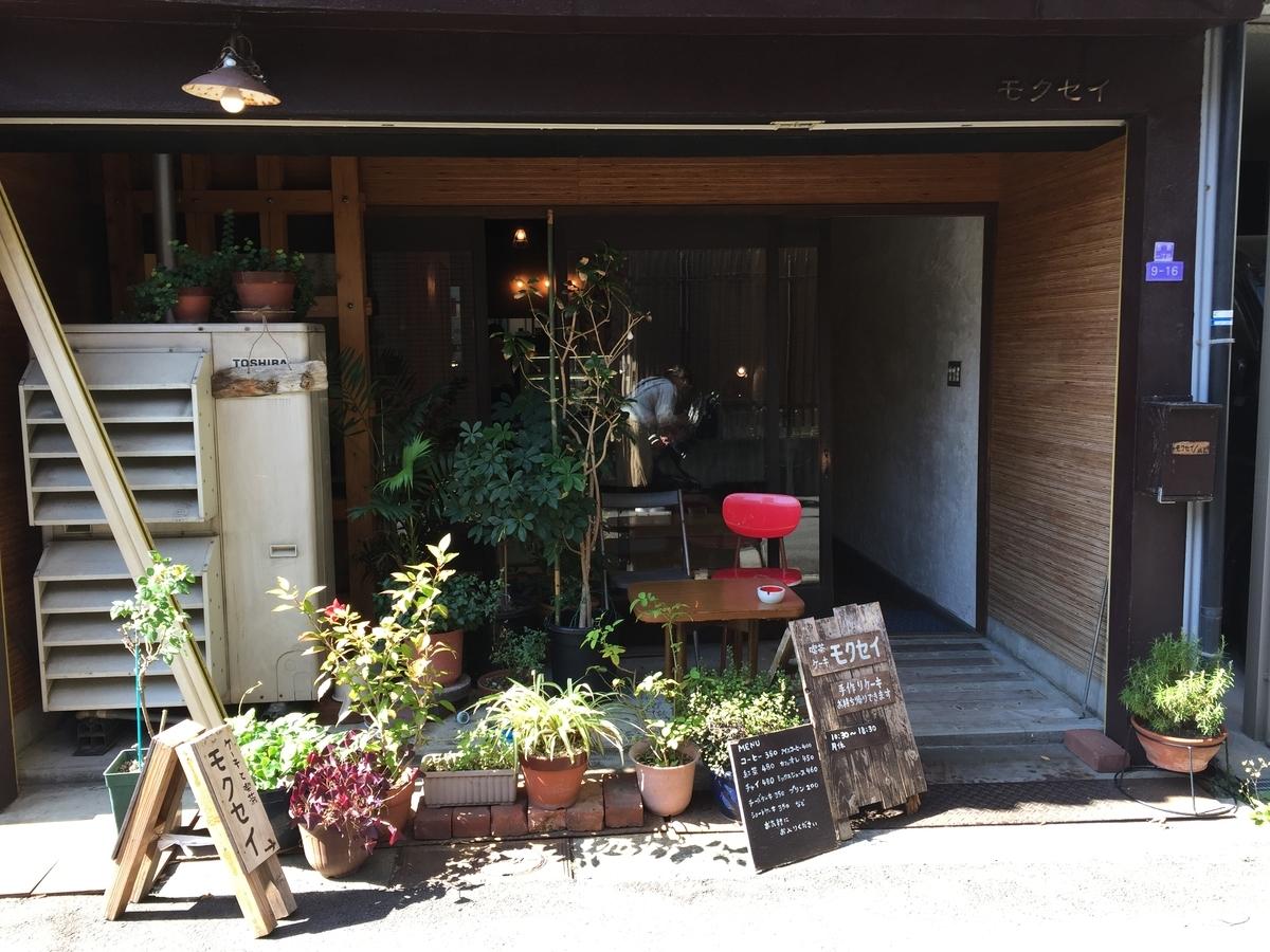 古民家を改装したたたずまいの喫茶店「モクセイ」入り口 店の前に植物の鉢が数個置かれている