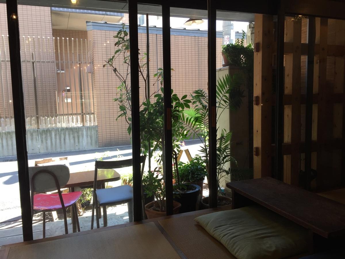 店内から入口のガラス戸越しの景色。入り口の鉢植えと喫煙席らしき灰皿の置かれたテーブルと椅子が一脚