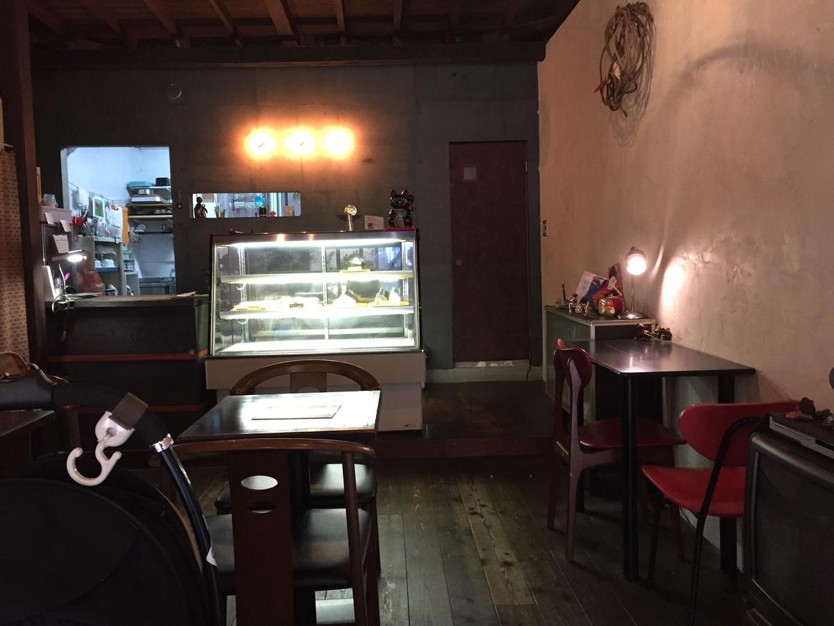 店内を入り口側から撮っている。テーブル席があり、奥にはケーキのショーケースとレジ、さらに奥にはキッチンが見える