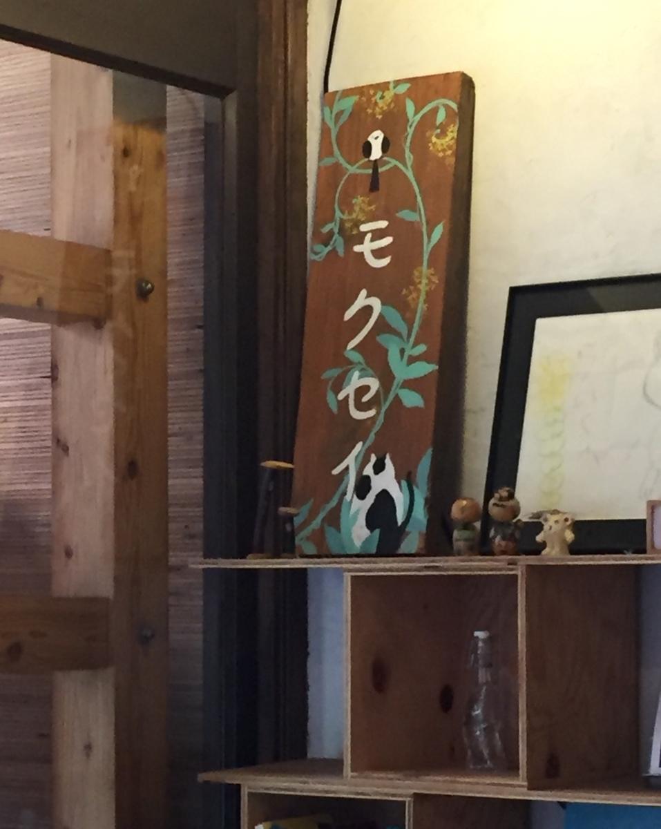 棚の上に飾られた「モクセイ」と書かれた小鳥と猫の絵の看板らしき板