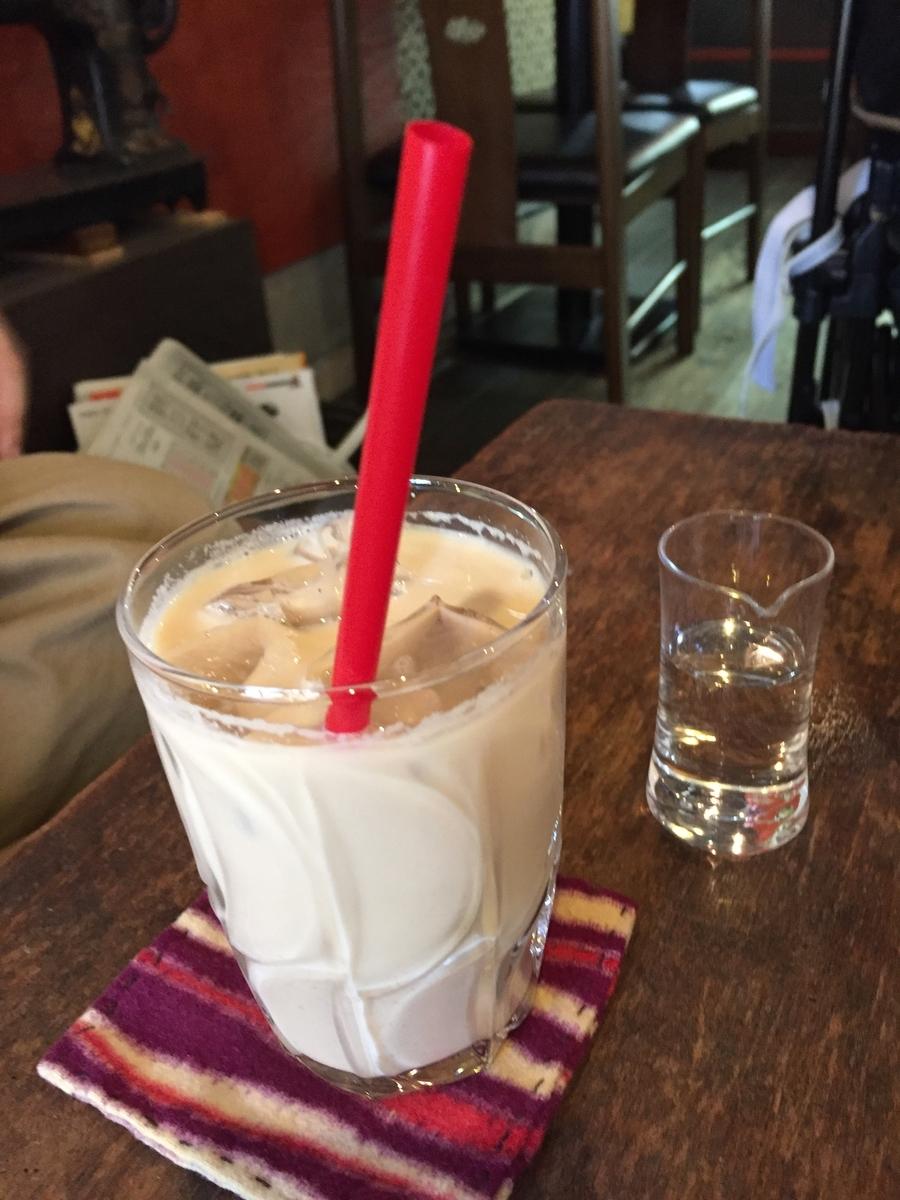 少し小さめのグラスになみなみと入った氷入りのベージュ色をしたチャイに赤いストローが入っている。傍にはシロップの入ったちいさなショットグラス